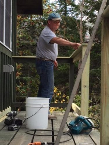 Rev. Jeff repairing cabin deck at Horton Center